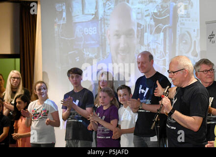 27 June 2018, Germany, Leverkusen: Pupils standing in the assembly hall of the Werner Heisenberg secondary school in order to pose questions to the astronaut Alexander Gerst (background), who is connected over radio. Short range radio frequency is used to make contact with the astronaut Alexander Gerst on the International Space Station ISS for eleven minutes. Photo: Henning Kaiser/dpa - Stock Photo