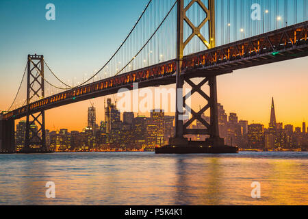 Classic panoramic view of San Francisco skyline with famous Oakland Bay Bridge illuminated in beautiful golden evening light at sunset in summer - Stock Photo