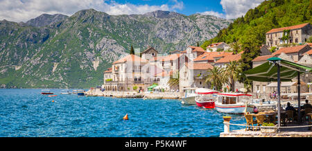 Scenic panorama view of the historic town of Perast at famous Bay of Kotor on a beautiful sunny day with blue sky and clouds in summer, Montenegro, so - Stock Photo
