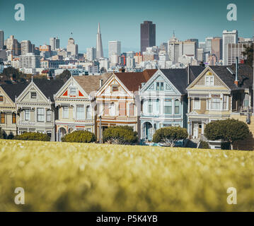 Classic postcard view of famous Painted Ladies, a row of colorful Victorian houses located at Alamo Square, with the skyline of San Francisco, USA - Stock Photo