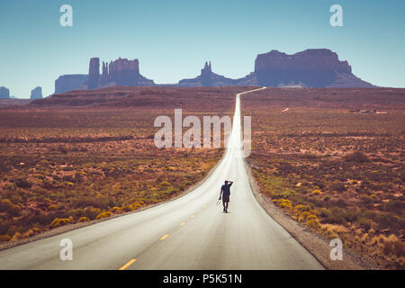 Classic panorama view of young person walking on famous Forrest Gump highway in Monument Valley at noon, Arizona, USA