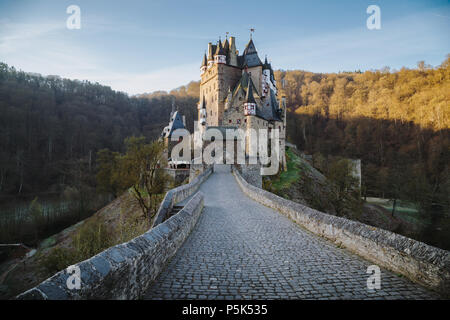 Beautiful view of famous Eltz Castle in scenic golden morning light at sunrise with blue sky on a sunny day in fall with retro vintage VSCO style filt - Stock Photo