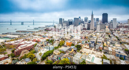 Classic aerial view of modern San Francisco skyline in summer with famous San Francisco fog rolling in seen from historic Coit Tower, San Francisco Ba - Stock Photo