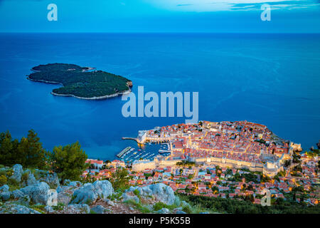 Panoramic aerial view of the historic town of Dubrovnik with Lokrum island in beautiful evening twilight at dusk, Dalmatia, Croatia - Stock Photo