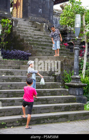 Boys playing on the steps of Besakih Temple, perched 1000m high on the Southwestern slopes of Mt Agung, Bali (also Mother Temple or Pura Besakih) - Stock Photo