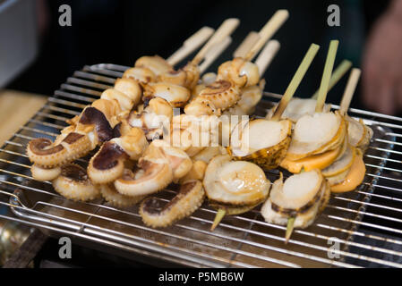 Grilled scallop and squid at Kuromon market Osaka Japan - Stock Photo