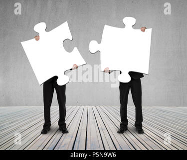 Businessmen holding two puzzles to connect on wooden floor - Stock Photo