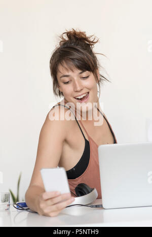 Young and pretty startup worker using a moblie phone at work - Stock Photo