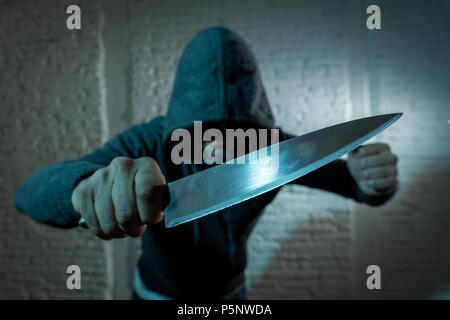 close up of a hands holding a knife of dangerous hooded man standing in the dark in London knife crime concept. - Stock Photo