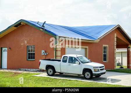 Fort Ft. Myers Florida Lehigh Acres after Hurricane Irma storm wind damage destruction aftermath blue tarp waterproof covering roof house home residen - Stock Photo