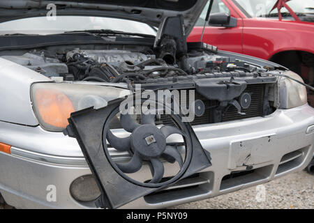 The engine compartment of a wrecked car with selective focus on the radiator fan hanging out of the front of it - Stock Photo