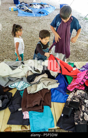 Florida LaBelle after Hurricane Irma storm assistance relief donations free clothing distribution site point Hispanic boy girl siblings looking - Stock Photo