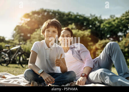 Boy showing thumb up and sitting with his dad - Stock Photo