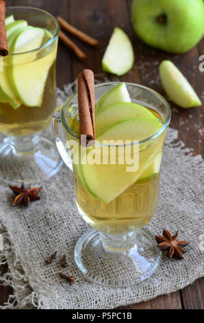 Apple and cinnamon hot drink on wooden background - Stock Photo