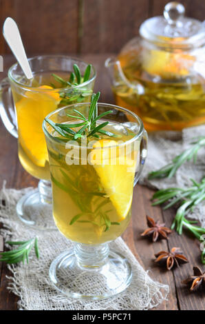 Healthy orange and rosemary tea on wooden background - Stock Photo