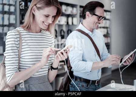 Two young friends looking at different gadgets in a shop - Stock Photo