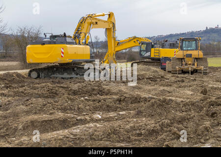 two yellow excavators at a loamy construction site - Stock Photo