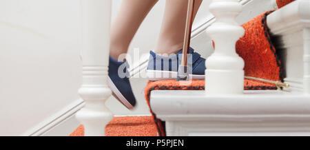 ältere Frau geht die Treppe hinauf mit Stock, elderly Person on stairs with stick - Stock Photo