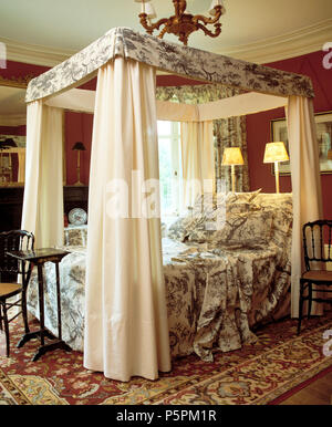 Toile-de-Jouy patterned bed-cover and pillows on four-poster bed with cream drapes in country bedroom with lighted lamps behind bed - Stock Photo