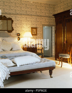 Pale blue sofa at the foot of bed with white linen in French country bedroom with Toile-de-Jouy wallpaper - Stock Photo
