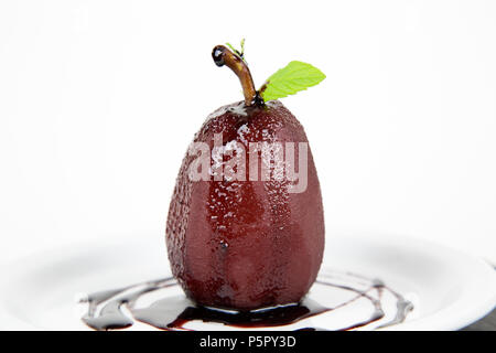 Poached pear in red wine and cinnamon on plate - Stock Photo