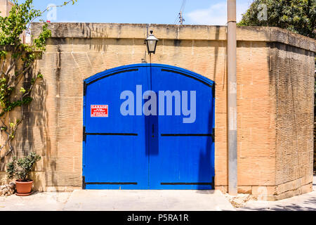 Blue garage door in Gozo, Malta with a sign saying no parking. - Stock Photo