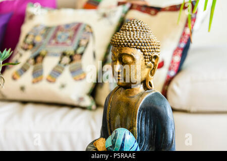 Statue of contemplating Buddha inside a modern, trendy house with eastern interior design influences. - Stock Photo