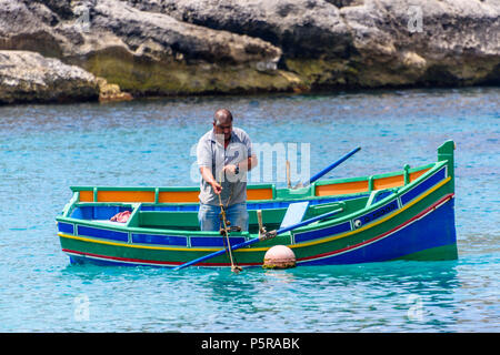 A fisherman rows his traditional Maltese rowing boat out in Xlendi bay to collect lobster cages. - Stock Photo