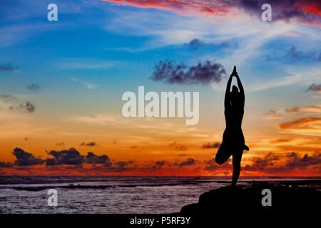 Sunset meditation silhouette Active woman stand in yoga pose on beach rock to keep fit and health. Healthy lifestyle, fitness training, sport activity - Stock Photo