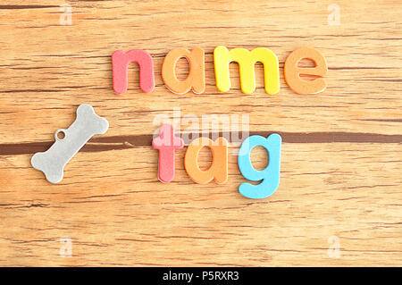 A bone shape name tag for a dog with the word name tag - Stock Photo