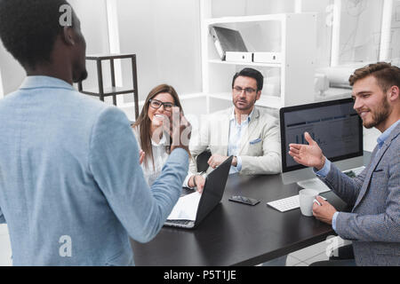 businessman talking with colleagues in the workplace - Stock Photo