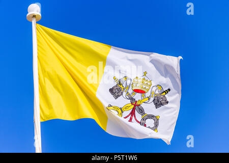 The flag of the Vatican City against a blue sky. - Stock Photo