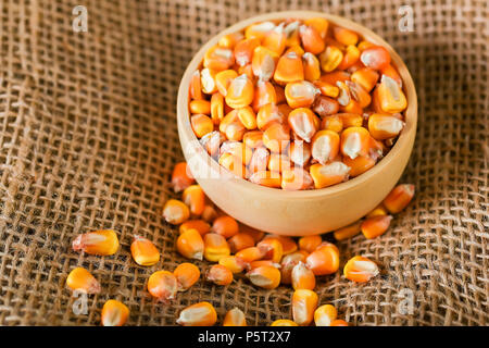 Close up corn seeds in bowl on beige cloth - Stock Photo