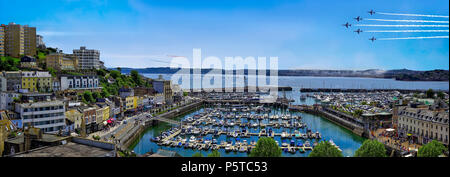 GB - DEVON: Red Arrows Team of the Royal Airforce above Torbay with Torquay harbour in foreground - Stock Photo
