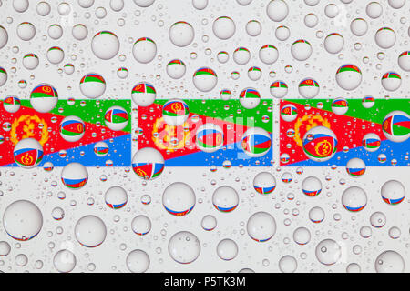 Flags  of Eritrea behind a glass covered with raindrops. - Stock Photo