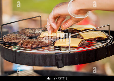 Man's hand, spread the cheese on the burgers - Stock Photo