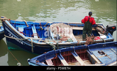 A fisherman preparing to go fishing in a traditional blue boat in Essaouira - Stock Photo