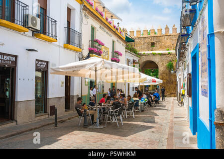 Cordoba Spain cafe, view of tourists relaxing on a cafe terrace in a street in the Juderia (old Jewish) quarter of Cordoba (Cordova) Andalucia, Spain. - Stock Photo