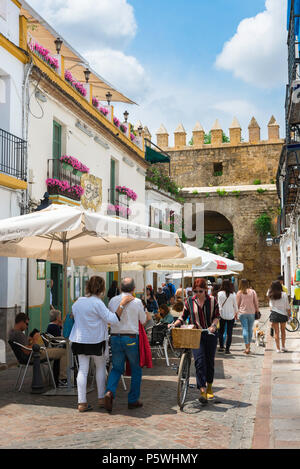 Cordoba cafe, view of people walking past a cafe terrace in a street in the Juderia (old Jewish) quarter of Cordoba (Cordova) Andalucia, Spain. - Stock Photo