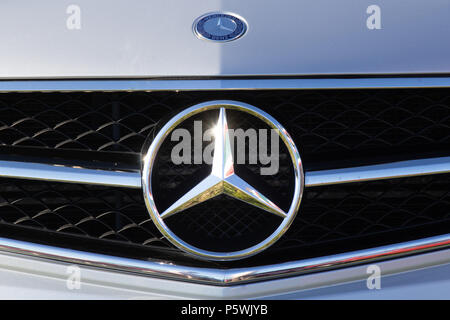 The three star badge on the front of a Mercedes-Benz car at a classic car show - Stock Photo