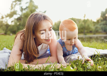 Mother and baby playing on grass in park. - Stock Photo