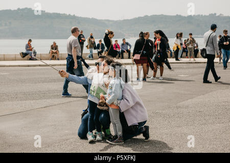 Portugal, Lisbon, May 1, 2018: A young Asian family father, mother and two daughters make an emotional selfie on the waterfront in Belem. People are walking around