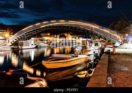 Arched bridge for pedestrians in Trogir, Croatia, Unesco. Night scene. Travel destination. Boats in the port. Yellow photo filter. - Stock Photo