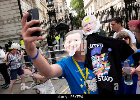 London, UK. 23rd June 2018. A protester wearing David Cameron and Boris Johnson masks takes a selfie outside 10 Downing Street. March for a Peoples Vo - Stock Photo