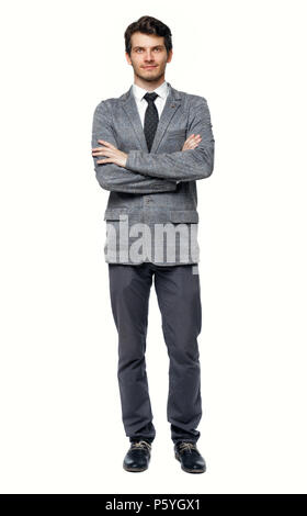 Smiling young businessman. Front view. A young specialist in a suit is standing with his arms folded on his chest. Isolated over white background - Stock Photo