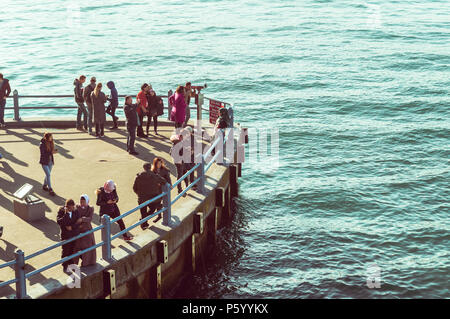 Istanbul, Turkey - January 06, 2018: People viewing seascape on the pier near Galata Bridge in Istanbul, Turkey. - Stock Photo