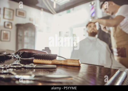 Accesories for cutting on the table in a barbershop and a hairdresser works in the background.  Photo in vintage style - Stock Photo