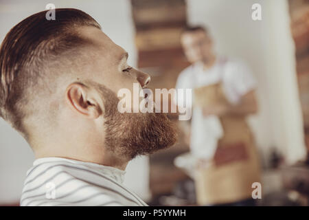 Close-up of man's face with a beard while he is waiting for a barber. Photo in vintage style - Stock Photo