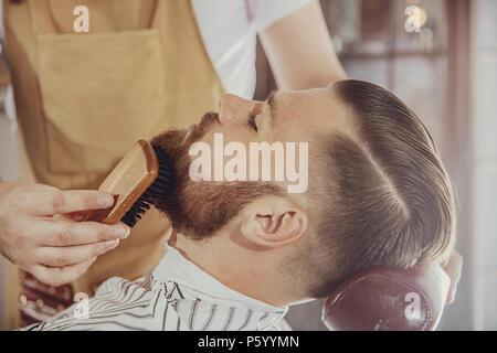 The barber combs the man's beard with a brush. Photo in vintage style - Stock Photo