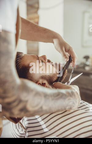 Barber cuts the client's beard with scissors and a comb. Photo in vintage style - Stock Photo